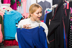 Girl choosing a trousers in sport store. Joyful smiling girl choosing new fitness pants in the sport store Stock Image