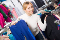 Girl choosing a trousers in sport store Royalty Free Stock Photography