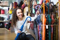 Girl choosing umbrella in shop Royalty Free Stock Photography