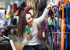 Girl choosing umbrella in shop Royalty Free Stock Photos