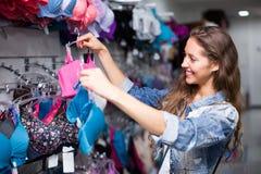 Girl choosing underwear at shop Stock Photos