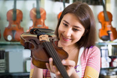 Girl choosing violin in music shop Royalty Free Stock Photo