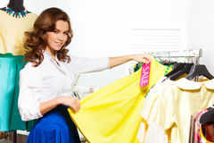 Girl choosing yellow skirt during sale in shop Royalty Free Stock Photography
