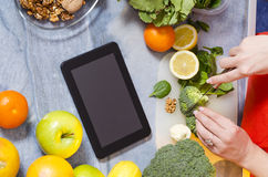 Girl chopping broccoli, copy space, tablet on counter Royalty Free Stock Photos