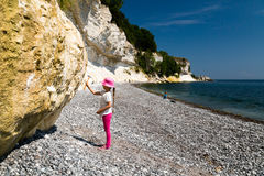 Girl chopping at chalk cliffs. The popular Danish tourist attraction Stevns Klint on a sunny summer day Stock Photo