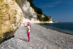 Girl chopping at chalk cliffs. The popular Danish tourist attraction Stevns Klint on a sunny summer day Stock Photography