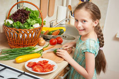 Girl chopping cucumber in kitchen, vegetables and fresh fruits in basket, healthy nutrition concept Royalty Free Stock Photo