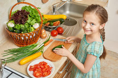 Girl chopping cucumber in kitchen, vegetables and fresh fruits in basket, healthy nutrition concept Royalty Free Stock Images