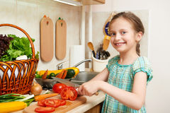Girl chopping tomatoes, vegetables and fresh fruits in kitchen interior, healthy food concept Stock Images
