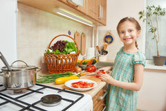 Girl chopping tomatoes, vegetables and fresh fruits in kitchen interior, healthy food concept Royalty Free Stock Images