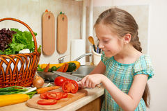 Girl chopping tomatoes, vegetables and fresh fruits in kitchen interior, healthy food concept Stock Photo