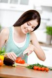 Girl chops groceries for salad Stock Photography