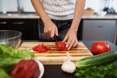 Girl chops tomato on salad Royalty Free Stock Photos