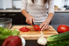 Girl chops tomato on salad in the kitchen Stock Image