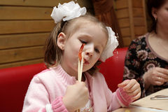 Girl with chopsticks. The girl eats a shrimp in cafe Stock Photo