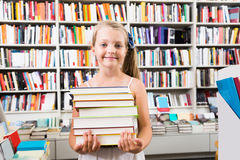 Girl chose a lot of books in the library. Child girl chose a lot of books in the library Stock Images