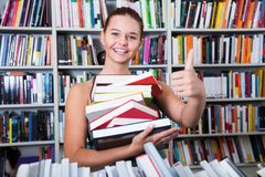 Girl chose a lot of books in university library. Brunete girl chose a lot of books in university library shows thump up Stock Photography