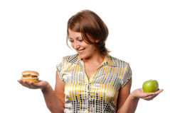 Girl is chosen between apple and hamburger Royalty Free Stock Photography
