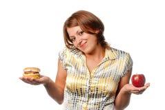 Girl is chosen between apple and hamburger Royalty Free Stock Photos