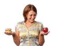 Girl is chosen between apple and hamburger Stock Photo