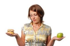 Girl is chosen between apple and hamburger Royalty Free Stock Photo