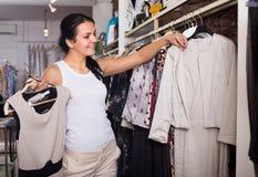 Girl chousing dress Stock Photos