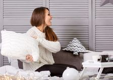 Girl in christmas beats pillows playing at home. The concept of a holiday, coziness and Christmas Royalty Free Stock Image