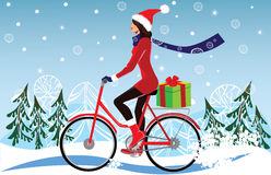 Girl in a Christmas cap, on bicycle carries gifts, winter, winter landscape Royalty Free Stock Images
