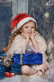 Girl in a Christmas cap with a gift Stock Photography