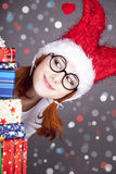 Girl in christmas cap with gift boxes. Royalty Free Stock Photography