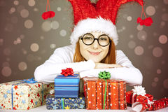 Girl in christmas cap and glasses with gift boxes. Royalty Free Stock Photos