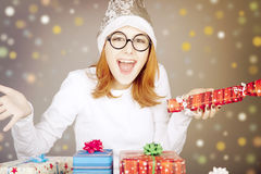Girl in christmas cap and glasses with gift boxes. Stock Images