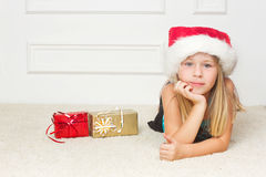 Girl in a Christmas cap lies Royalty Free Stock Image