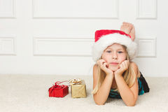Girl in a Christmas cap lies Stock Photos