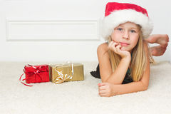 Girl in a Christmas cap lies Royalty Free Stock Photos