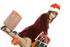 The girl in a Christmas cap with purchases Royalty Free Stock Photos