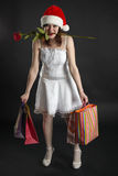 Girl in Christmas cap, with purchases and rose Stock Photos