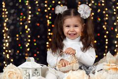 Girl in christmas decoration with gift, dark background with illumination and boke lights, winter holiday concept Royalty Free Stock Photos