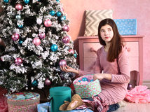 Girl with christmas decoration and tree Stock Image