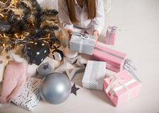 Girl at Christmas dreams near the Christmas tree with gifts, the concept of a holiday, coziness and Christmas. stock images