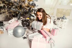 Girl at Christmas dreams near the Christmas tree with gifts, the royalty free stock images