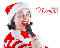 Girl in Christmas dress singing into a microphone Royalty Free Stock Image