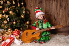 Girl - the Christmas elf with a guitar Royalty Free Stock Photo