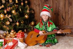 Girl - the Christmas elf with a guitar Stock Photos