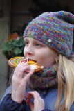 The girl at the Christmas fair eating Christmas cookies Stock Photo