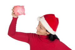 Girl at Christmas flipping a piggy bank Royalty Free Stock Photos