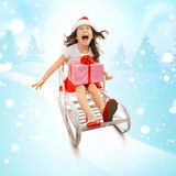 Girl with Christmas gift box on a sled Royalty Free Stock Photos