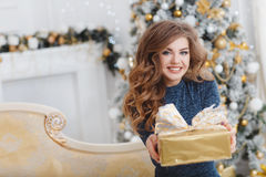 Girl with Christmas gift near beautiful dressed Christmas tree Stock Images