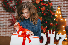 Girl with Christmas gift near beautiful dressed Christmas tree Royalty Free Stock Image