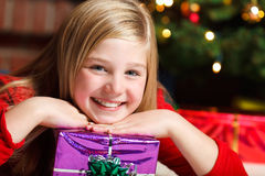 Girl with christmas gift smiling Royalty Free Stock Images